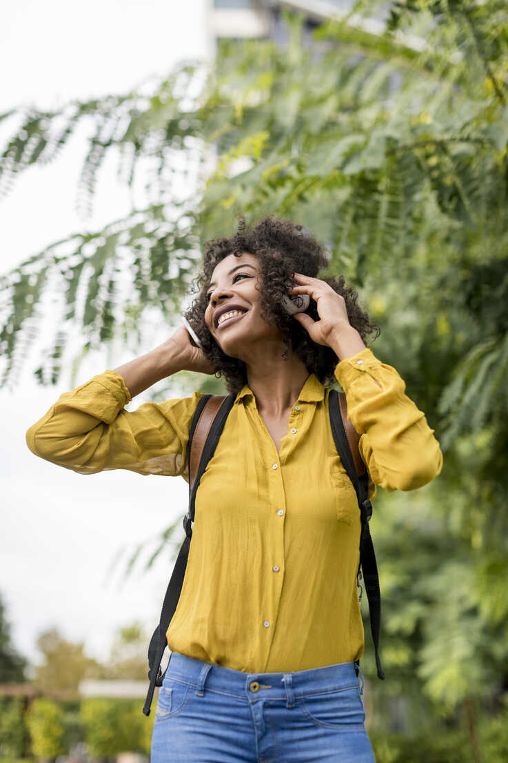 Happy woman listening music with headphones outdoors - MAUF02346 - Mauro Grigollo/Westend61
