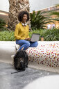 Portrait of smiling woman sitting on bench using laptop - MAUF02358