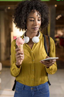 Portrait of woman with ice cream cone looking at cell phone - MAUF02361