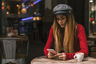 Portrait of young woman text messaging on terrace of a coffee shop - ACPF00370