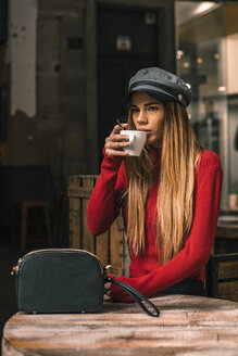 Portrait of young woman sitting on terrace of a cafe drinking coffee - ACPF00373