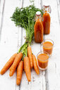 Carrots, glasses of carrot juice and swing top bottles on wood - LVF07661