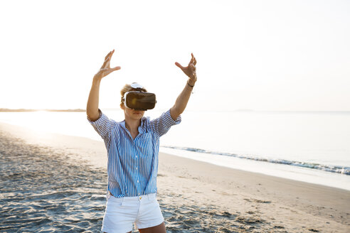 Blonde woman doing kind of yoga exercises on a beach in thailand with 3D virtual reality goggles - HMEF00176
