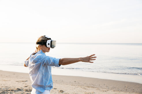 Blonde woman doing kind of yoga exercises on a beach in thailand with 3D virtual reality goggles - HMEF00179