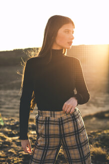 Portrait of fashionable teenage girl wearing black pullover and checked trousers at sunset - ACPF00376