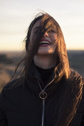 Portrait of a pretty brunette girl smiling with her hair on her face during sunset in Spain - ACPF00379