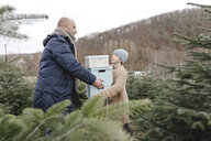 Father and son carrying gift boxes on a Christmas tree plantation - KMKF00724