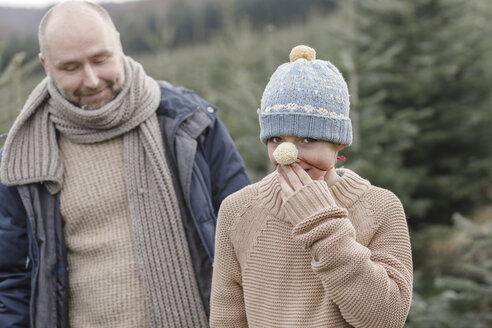 Arnsberg, NRW, Deutschland.Ein Jugendlicher in einer handgestrickte Mütze spielt mit seinem Vater auf der Weihnachtsbaum-Plantage - KMKF00733