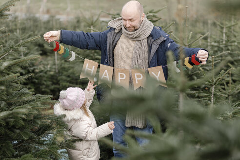 Father with daughter holding decoration on a Christmas tree plantation - KMKF00736
