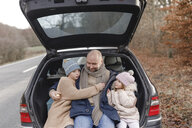 Smiling father with two children sitting in car trunk at the roadside - KMKF00748