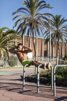 Barechested muscular man doing sit-ups outdoors - MAUF02364