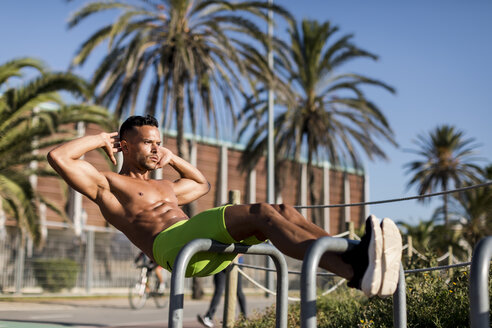 Barechested muscular man doing sit-ups outdoors - MAUF02367