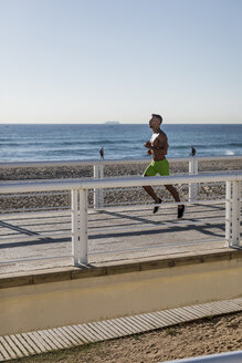 Barechested man running on waterfront promenade - MAUF02370