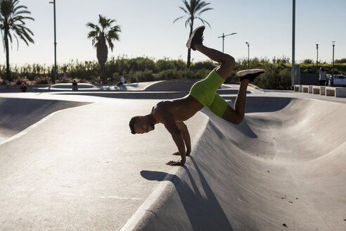Barechested muscular man exercising in a skatepark - MAUF02376