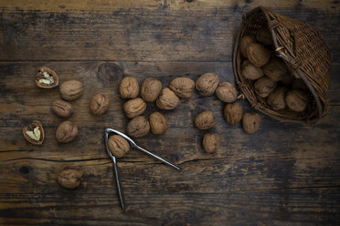Wickerbasket, whole and cracked walnuts and nutcracker on wood - LVF07668