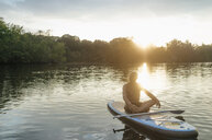 Senior man sitting on SUP board at sunset - GUSF01784