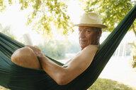 Senior man wearing straw hat relaxing in hammock at lakeshore - GUSF01787
