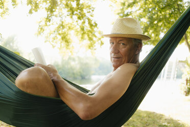 Senior man wearing straw hat relaxing in hammock at lakeshore - GUSF01787
