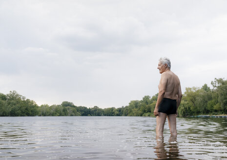 Senior man standing in a lake - GUSF01790