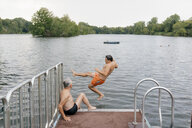 Man jumping from jetty into a lake - GUSF01796