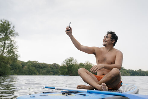 Man sitting on SUP board on a lake taking a selfie - GUSF01799