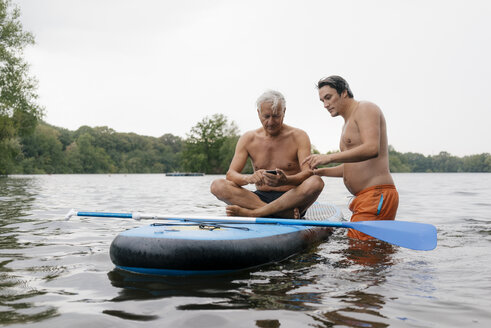 Older and younger man with SUP board on a lake using cell phone - GUSF01802