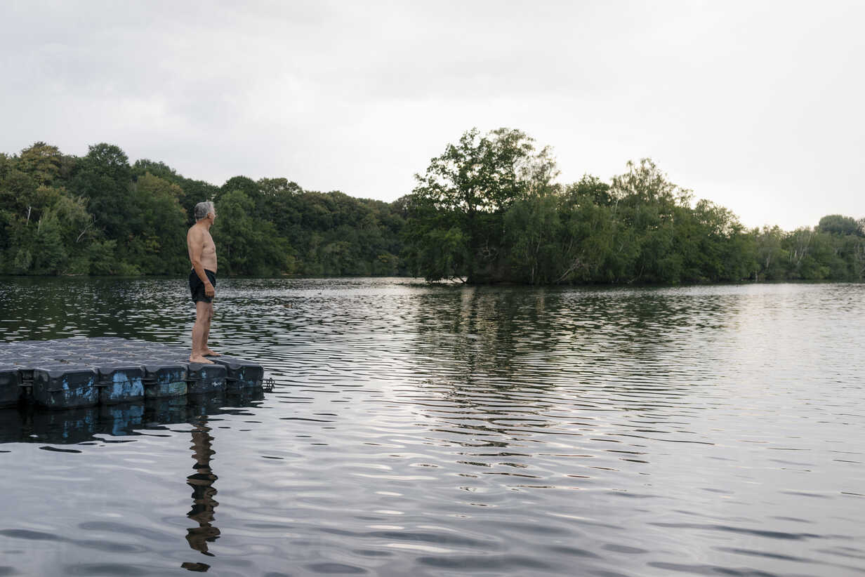 Senior man standing on raft in a lake - GUSF01805 - Gustafsson/Westend61