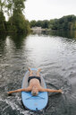 Senior man lying on SUP board on a lake - GUSF01808