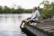 Senior man sitting on jetty at a lake - GUSF01811