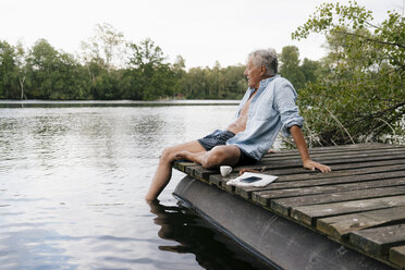 Senior man sitting on jetty at a lake - GUSF01811