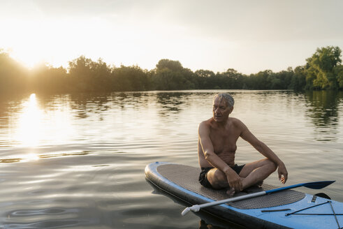 Senior man sitting on SUP board at sunset - GUSF01817