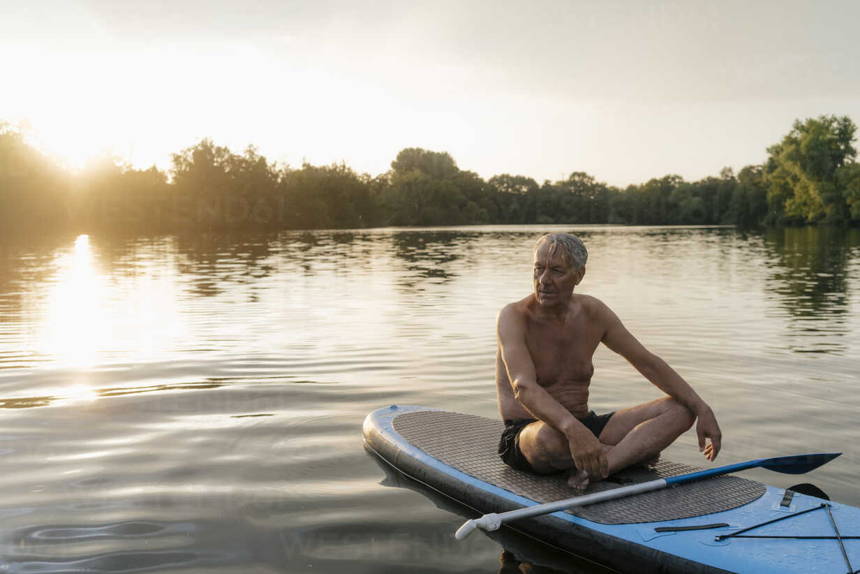 Senior man sitting on SUP board at sunset - GUSF01817 - Gustafsson/Westend61