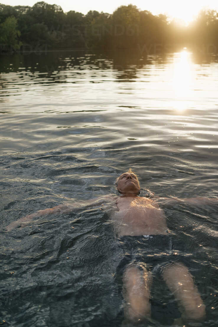 Senior man swimming in a lake at sunset - GUSF01820 - Gustafsson/Westend61