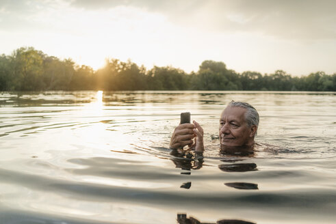 Senior man swimming in a lake at sunset using cell phone - GUSF01823
