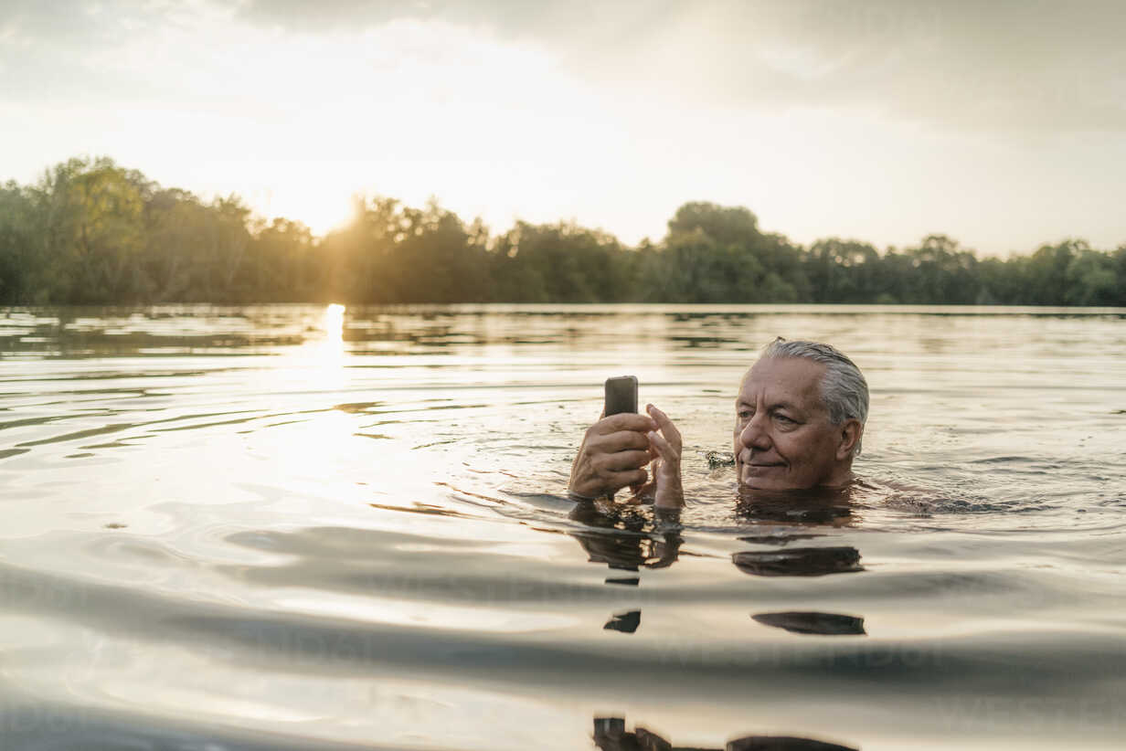 Senior man swimming in a lake at sunset using cell phone - GUSF01823 - Gustafsson/Westend61