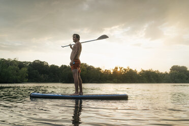 Man standing on SUP board on a lake at sunset - GUSF01826