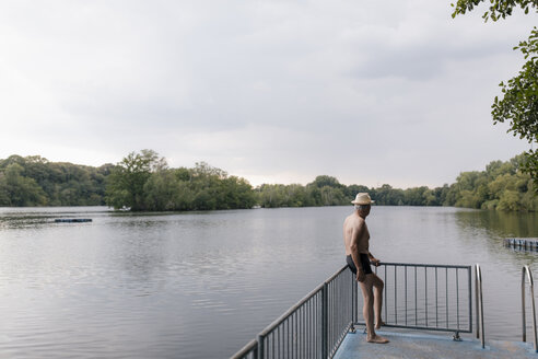 Senior man wearing straw hat standing at a lake - GUSF01832