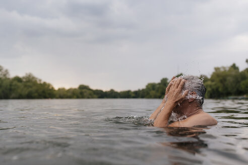 Senior man in a lake splashing water in his face - GUSF01835