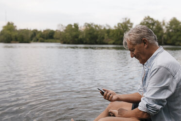 Senior man sitting at a lake using cell phone - GUSF01844