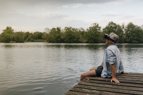 Senior man sitting on jetty at a lake wearing VR glasses - GUSF01847