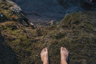 Feet of a man standing at the lakeside - GUSF01850