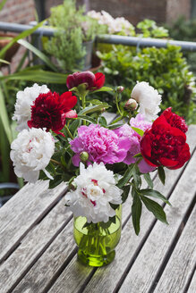 Bunch of white, red and pink Peonies in vase on garden table - GWF05793