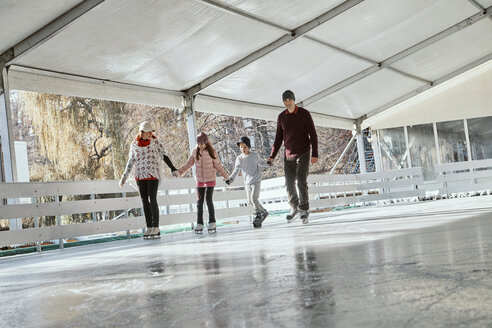Family with two kids ice skating on the ice rink - ZEDF01786