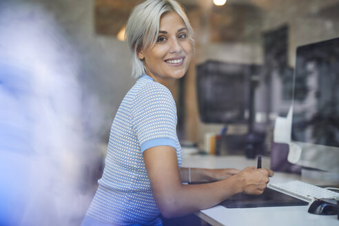 Young woman working in office, sitting at desk, smiling - PNEF01132
