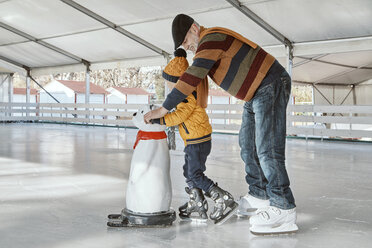 Grandfather and grandson on the ice rink, ice skating, using ice bear figure as prop - ZEDF01803