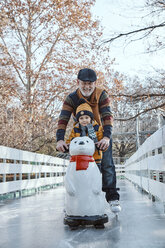 Grandfather and grandson on the ice rink, ice skating, using ice bear figure as prop - ZEDF01806
