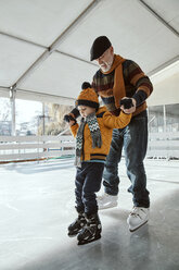 Grandfather and grandson on the ice rink, ice skating - ZEDF01809