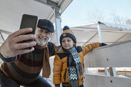 Grandfather and grandson on the ice rink, taking selfies - ZEDF01815