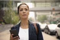 Businesswoman using smart phone on urban sidewalk - HEROF06186