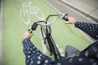 Businessman commuter riding bicycle in urban bike lane - HEROF06222